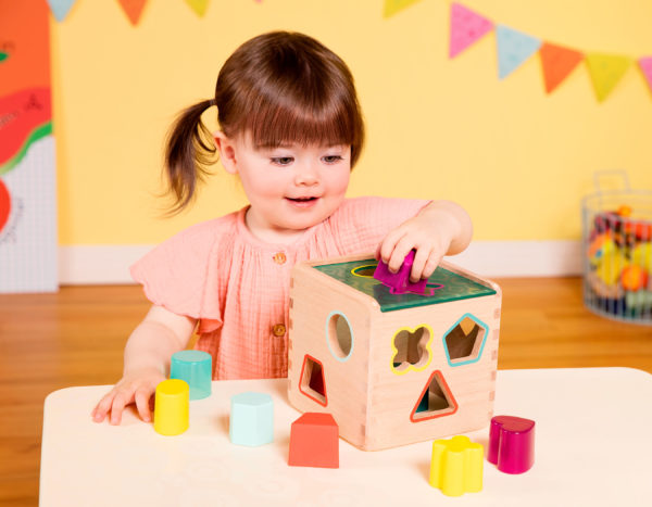 Girl with shape sorter cube.
