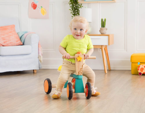 Boy on a toddler bike in a room.