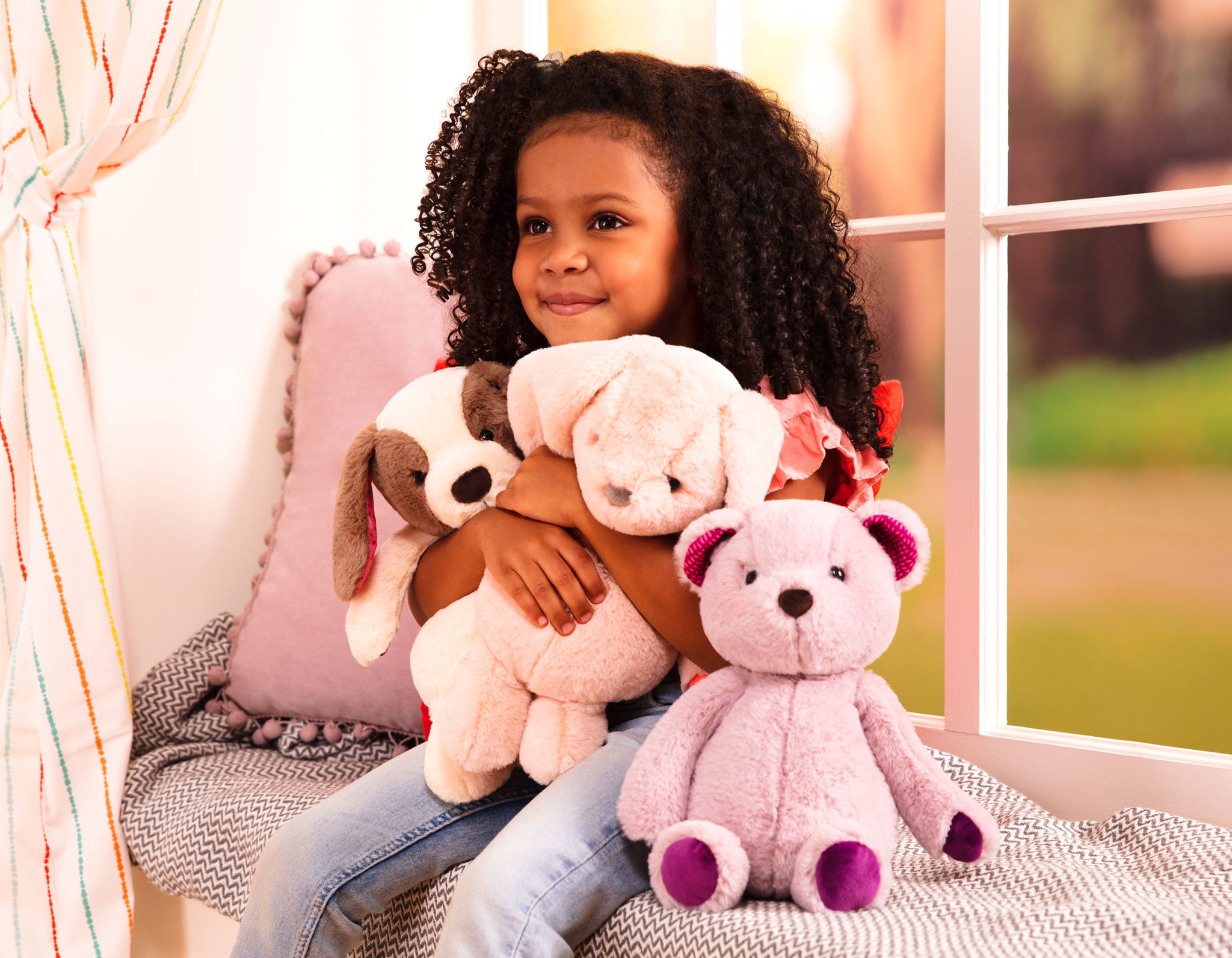 Girl and three stuffed animal toys.
