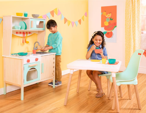 Smiling boy pretend washing dishes in play kitchen and smiling girl pretend eating from kids dishes while sitting at a kids table.