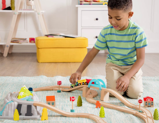 Boy playing with a train set.