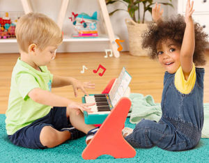 Toddlers playing on a toy piano.