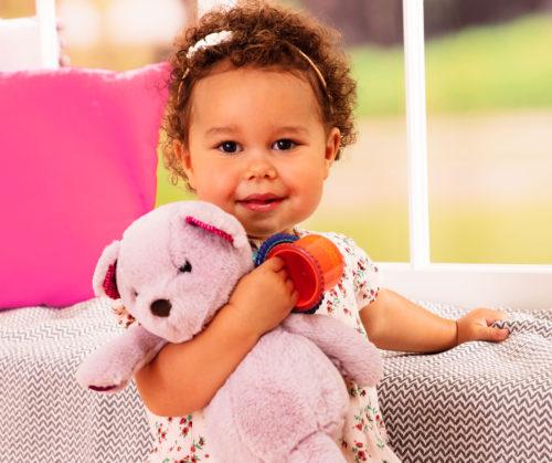 Smiling baby girl cuddling a purple teddy bear.