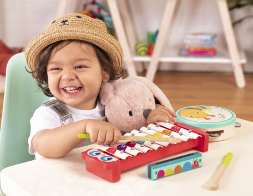 Smiling boy playing on a toy xylophone.