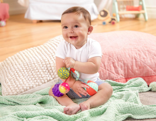 Smiling baby with ball toys.
