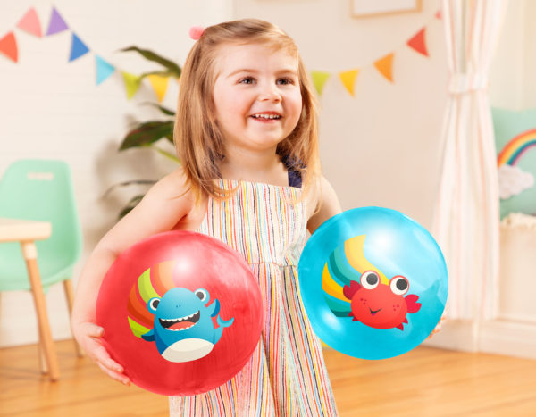 Smiling girl with two bouncy balls.