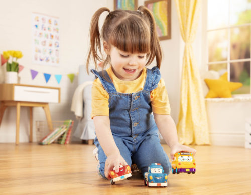 Smiling girl playing with 3 toy cars.