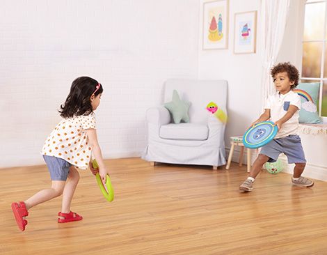 Boy and girl playing a paddle game.