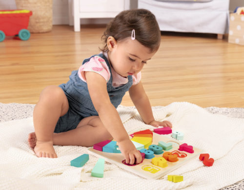 Girl playing with a colorful number puzzle.