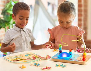 Two kids with wire maze and peg puzzle.