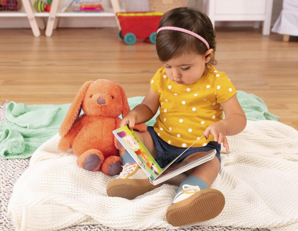 Girl looking through a board book.
