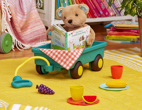 Teddy bear in wagon with book and play food.