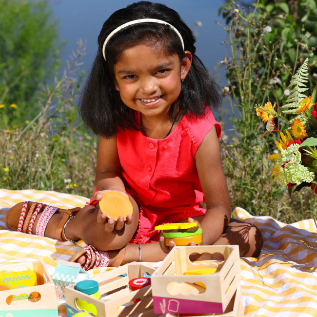 Girl playing with wooden play food.