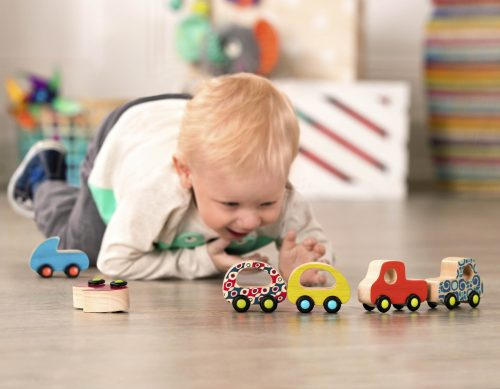 Boy with toy wooden cars.