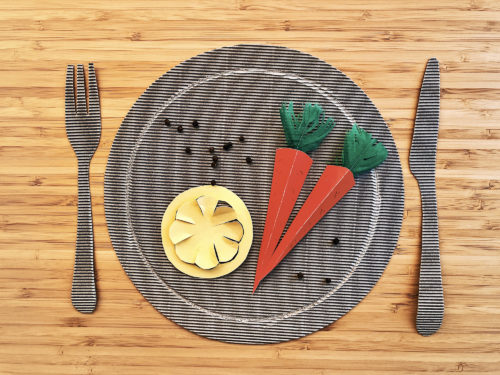 Paper fork, plate and knife with paper carrots and a paper lemon.
