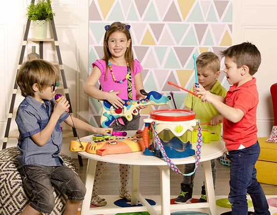 A boy singing and playing a cat piano, a smiling girl holding a dog guitar, a boy playing on a frog-shaped drum set, and a boy playing on a drum.