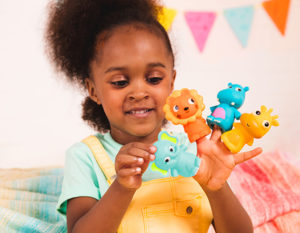 Smiling girl with four animal finger puppets on her hand.