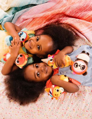 Two smiling girls with mini stuffed animals.