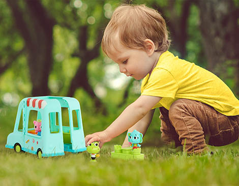 Boy playing with toy truck outside.