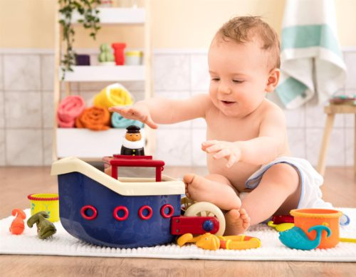 Baby boy playing with a toy boat and bath toys.